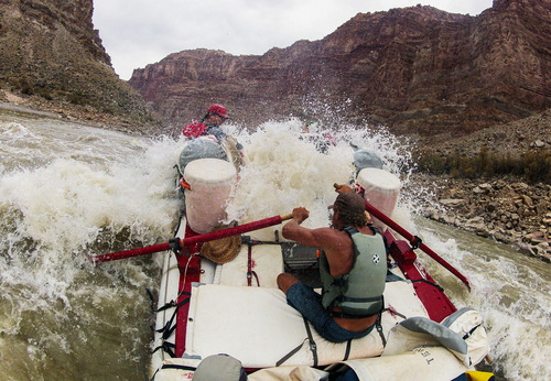Francisco Kjolseth  |  The Salt Lake Tribune Holiday River Expeditions river guide Alex Jahp powers through a large wave while navigating the rapids in Cataract Canyon.