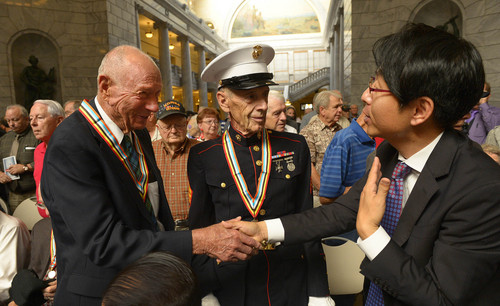 Leah Hogsten  |  The Salt Lake Tribune Don Lubeck of Clearfied (left) is thanked for his service by a member representing the government of The Republic of Korea (right).  WWII Marine veteran Gene Silotti (center) accepted a medal on behalf of his brother Jack Silotti, who served in the Korean War with the Marines and passed away two months ago.   One hundred eighty one Korean War veterans were presented with a medal from the government of The Republic of Korea and recognized for their service, Wednesday, September 10, 2014 in the Utah Capitol rotunda.