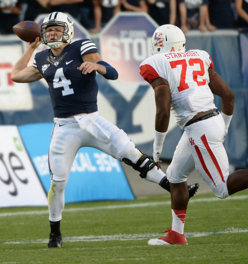 Steve Griffin  |  The Salt Lake Tribune   BYU Cougars quarterback Taysom Hill (4) throws an off balanced pass as Houston Cougars defensive end Gavin Stansbury closes in during game between BYU and Houston and LaVell Edwards Stadium in Provo, Thursday, September 11, 2014.