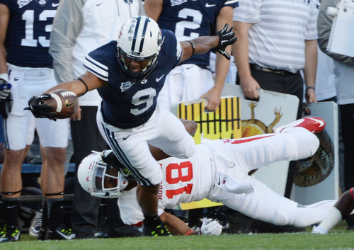 Steve Griffin  |  The Salt Lake Tribune   BYU Cougars wide receiver Jordan Leslie (9) tries to escape the tackle of Houston Cougars defensive back Lee Hightower (18) during game between BYU and Houston and LaVell Edwards Stadium in Provo, Thursday, September 11, 2014.