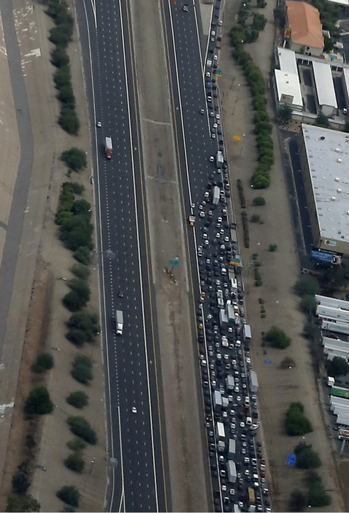 Arizona Department of Transportation detours all eastbound I-10 traffic at 43rd Ave following heavy rains and flooding that left motorists stranded during their morning commute on Monday, Sept. 8, 2014 in Phoenix. Monday's record breaking rainfall flooded several Phoenix-area freeways and local streets forcing closures with some areas reporting up to five inches of rain. (AP Photo/Matt York)
