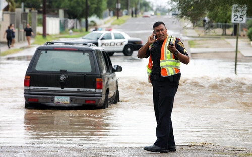 A police officer communicates at the scene where a vehicle is stranded in floodwaters in Tucson, Ariz., on Monday Sept. 8, 2014. The occupants were walked out by Tucson firefighters. Gov. Jan Brewer has declared a statewide emergency in Arizona's most populous county because of flooding from major storms that dropped record rainfall. (AP Photo/Arizona Daily Star, Rick Wiley) LOCAL TV OUT; MANDATORY CREDIT
