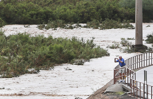 A man takes a picture of the torrents of monsoon storm runoff in the Rillito River near North Craycroft Road south of East River Road on Monday, Sept. 8, 2014, in Tucson, Ariz. (AP Photo/Arizona Daily Star, Mike Christy)