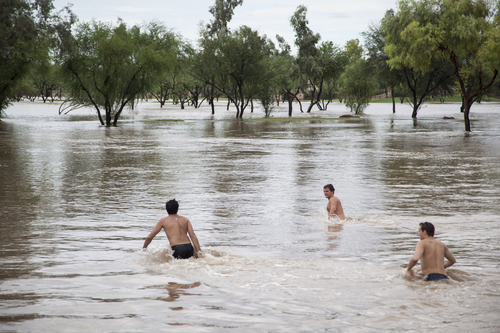 Saguaro High School Seniors, from left, Brad Khnanisho, Michael Panka and Shaun Younger spend time time in the Indian Bend Wash during the flooding in Scottsdale, Monday, Sept. 8, 2014.  (AP Photo/The Arizona Republic, Dave Seibert) MARICOPA COUNTY OUT - NO MAGS- NO SALES - MANDATORY CREDIT