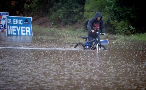 Construction worker Jason Haight Jr. makes his way back home, through high water at 54th Street and Camelback Avenue, Monday, Sept. 8, 2014, in Phoenix. Haight and his father rode to their construction site only to find work canceled for the day. (AP Photo/The Arizona Republic, Charlie Leight)