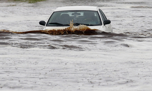 A vehicle tries to navigate a severely flooded street as heavy rains pour down Monday, Sept. 8, 2014, in Phoenix. Storms that flooded several Phoenix-area freeways and numerous local streets during the Monday morning commute set an all-time record for rainfall in Phoenix in a single day. (AP Photo/Ross D. Franklin)