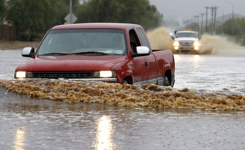 Drivers attempt to navigate their vehicles through severely flooded streets as heavy rains pour down Monday, Sept. 8, 2014, in Phoenix. Storms that flooded several Phoenix-area freeways and numerous local streets during the Monday morning commute set an all-time record for rainfall in Phoenix in a single day. (AP Photo/Ross D. Franklin)