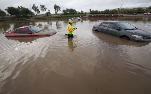Arizona Department of Transportation (ADOT) worker Carlos Parra looks for drains to clear flood waters on I-10 east at 43rd Ave. after monsoon rains flooded the freeway in Phoenix, Monday, Sept. 8, 2014. Heavy storms pounded the Phoenix area early Monday, flooding major freeways, prompting several water rescues and setting an all-time single-day record for rainfall in the desert city. (AP Photo/The Arizona Republic, Michael Chow) MARICOPA COUNTY OUT - NO MAGS- NO SALES - MANDATORY CREDIT