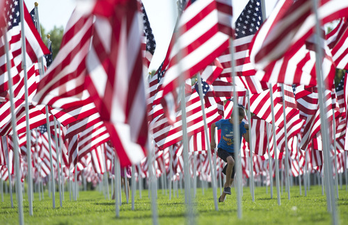 Steve Griffin  |  The Salt Lake Tribune Children play in a field of over 3,000 seven-foot- tall U.S. flags as they sway in the breeze outside Sandy City Hall in Sandy, Utah, Wednesday, September 10, 2014.  Homes for Heroes and the Colonial Flag Foundation have sponsored Utahís 13th Annual Healing Field flag display to honor and remember the victims of the 9/11 terrorist attacks. Each flag representing a life lost in horrific attacks.