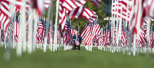 Steve Griffin  |  The Salt Lake Tribune   Lynne Strickling sits in a field of over 3,000 seven-foot- tall U.S. flags as they sway in the breeze outside Sandy City Hall in Sandy, Utah, Wednesday, September 10, 2014.  Homes for Heroes and the Colonial Flag Foundation have sponsored Utah's 13th Annual Healing Field flag display to honor and remember the victims of the 9/11 terrorist attacks. Each flag representing a life lost in horrific attacks.