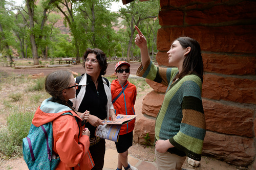 Franciso Kjolseth  |  The Salt Lake Tribune Visiting from Paris, Francoise Chanudet, center left, is joined by her kids Justine, 12, and Sylvain, 10, as they learn about the Grotto, one of the first historic buildings at Zion National Park that is now used by the Artist In Residence. Rachel Panitch, a fiddle player from Boston, was the first musician to participate in the program.