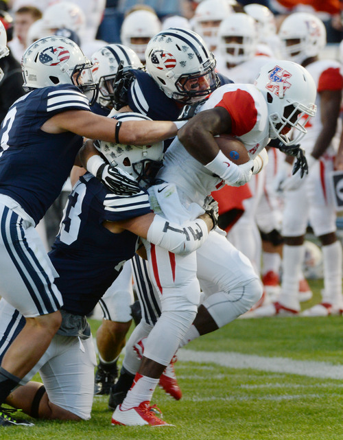 Steve Griffin  |  The Salt Lake Tribune   The BYU defense gang tackle Houston Cougars wide receiver Demarcus Ayers (10) during game between BYU and Houston and LaVell Edwards Stadium in Provo, Thursday, September 11, 2014.