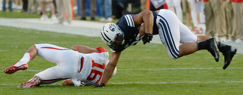 Steve Griffin  |  The Salt Lake Tribune   BYU Cougars running back Paul Lasike (33) gets knocked into the air by Houston Cougars defensive back Adrian McDonald (16) during game between BYU and Houston and LaVell Edwards Stadium in Provo, Thursday, September 11, 2014.