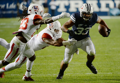Steve Griffin  |  The Salt Lake Tribune   BYU Cougars running back Paul Lasike (33) runs past the Houston defense in the second half of the  game between BYU and Houston and LaVell Edwards Stadium in Provo, Thursday, September 11, 2014.