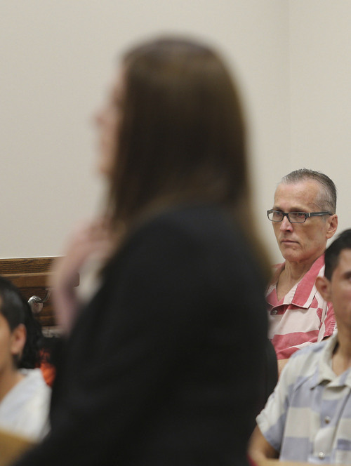Martin Joseph MacNeill (background with glasses) watches as his daughter,  Alexis MacNeill Somers,  asks the judge to give her father the maximum sentence as he is sentenced in a forcible sex abuse case by Judge Samuel D. McVey in Fourth District Court, MacNeill is also charged with killing his wife, Michelle MacNeill, in a separate case and is scheduled to be sentenced this Friday,  Monday, Sept. 15, 2014, in Provo.