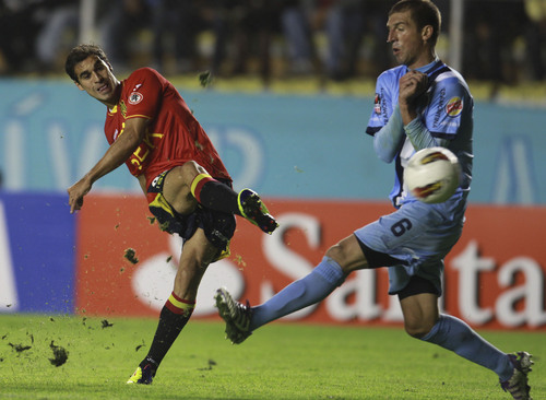 Sebastian Jaime of Chile's Union Espanola, left, kicks the ball past Pablo Frontini of Bolivia's Bolivar during their Copa Libertadores soccer match in La Paz Bolivia, Tuesday Feb. 21, 2012. (AP Photo/Juan Karita)