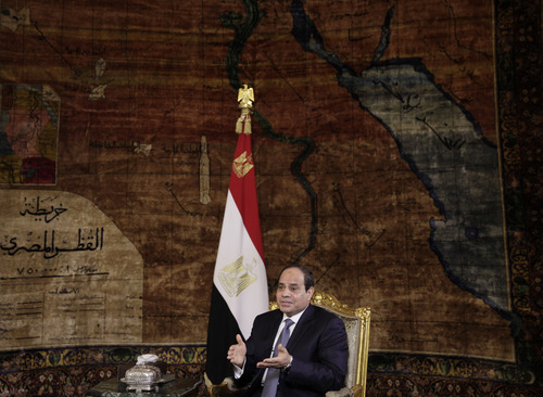 Egyptian President Abdel-Fattah el-Sissi speaks to The Associated Press during an interview at the presidential palace in Cairo, Saturday, Sept. 20, 2014. In the background is a 1930s era carpet depicting a map of Egypt. In his first interview with foreign media since taking office in June, el-Sissi has told AP he is prepared to give whatever support is needed in the fight against the Islamic State group but says military action is not the only answer. (AP Photo/Maya Alleruzzo)