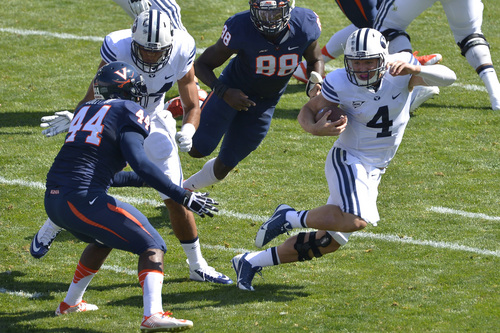 Chris Detrick  |  The Salt Lake Tribune Brigham Young Cougars quarterback Taysom Hill (4) runs past Virginia Cavaliers linebacker Henry Coley (44) and Virginia Cavaliers linebacker Max Valles (88) during the game at LaVell Edwards Stadium Saturday September 20, 2014.  Virginia is winning the game 16-13 at halftime.