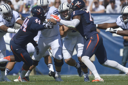Chris Detrick  |  The Salt Lake Tribune Brigham Young Cougars quarterback Taysom Hill (4) is tackled by Virginia Cavaliers linebacker Henry Coley (44) and Virginia Cavaliers defensive end Eli Harold (7) during the game at LaVell Edwards Stadium Saturday September 20, 2014.  Virginia is winning the game 16-13 at halftime.