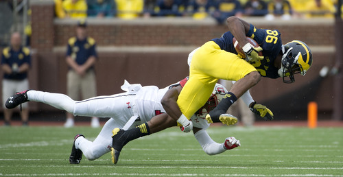 Jeremy Harmon  |  The Salt Lake Tribune  Michigan's Jehu Chesson (86) is tackled by Utah's Justin Thomas (12) as the Utes face the Wolverines in Ann Arbor, Saturday, Sept. 20, 2014.