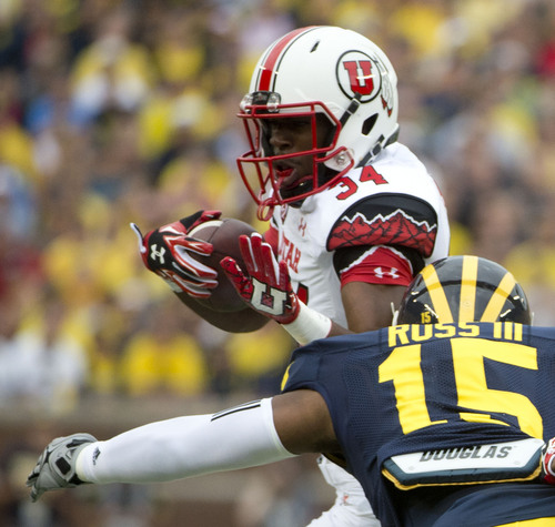 Jeremy Harmon  |  The Salt Lake Tribune  Utah's Bubba Poole (34) is tackled by Michigan's James Ross III (15) as the Utes face the Wolverines in Ann Arbor, Saturday, Sept. 20, 2014.