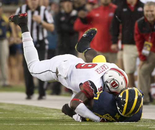 Jeremy Harmon  |  The Salt Lake Tribune  Utah's Tevin Carter (9) tackles Michigan's Derrick Green (27) as the Utes face the Wolverines in Ann Arbor, Saturday, Sept. 20, 2014.