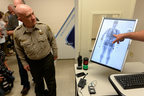 "Francisco Kjolseth  |  The Salt Lake Tribune The Salt Lake County Sheriff's Office announces the implementation of a new system to detect contraband as Lt. Dave Hall, left, has a look at his image for demonstration purposes. The SecurPASS Whole Body Contraband Detection System uses ""transmission imaging"" technology that is less intrusive because it does not show facial features or private body parts."