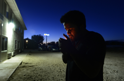Scott Sommerdorf   |  The Salt Lake Tribune Kunal Sah lights a cigarette behind the Green River Ramada Inn that he manages, Wednesday, September 16, 2014. He had earlier fixed the light that illuminates the sandy back yard of the motel.