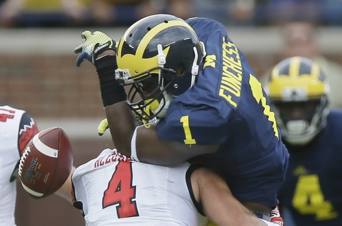 Utah defensive back Brian Blechen (4) knocks the ball away from Michigan wide receiver Devin Funchess (1) during the first half of an NCAA college football game in Ann Arbor, Mich., Saturday, Sept. 20, 2014.  (AP Photo/Carlos Osorio)