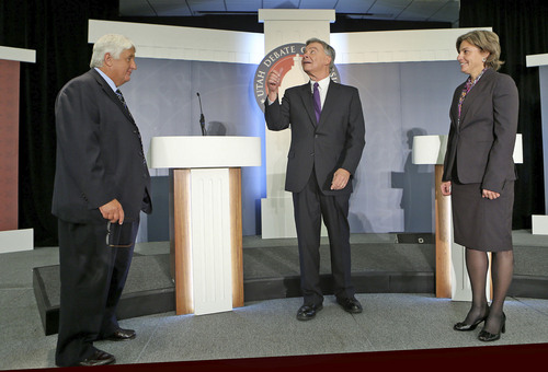 Moderator Ken Verdoia flips a coin as as Republican Congressman Rob Bishop and Democratic challenger Donna McAleer  call the coin toss to choose order in the debate in the Utah Debate Commission's 1st Congressional District debate at Weber State University Tuesday, Sept. 23, 2014, in Ogden.