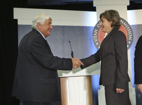Republican Congressman Rob Bishop and Democratic challenger Donna McAleer  shake hands after the coin toss  in the debate in the Utah Debate Commission's 1st Congressional District debate at Weber State University Tuesday, Sept. 23, 2014, in Ogden.