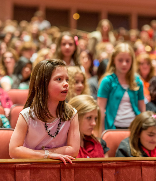 Trent Nelson  |  The Salt Lake Tribune Young girls stand during a talk by Primary General President Rosemary Wixom, at the LDS General Women's Meeting at the Conference Center in Salt Lake City, Saturday March 29, 2014. For the first time ever for Young Women and Relief Society and Primary will meet altogether, with every LDS female 8 and up invited.