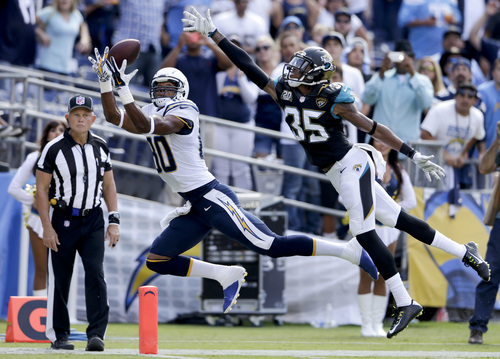 San Diego Chargers wide receiver Malcom Floyd, left, hauls in a touch down pass in front of Jacksonville Jaguars cornerback Demetrius McCray during the second of an NFL football game, Sunday, Sept. 28, 2014, in San Diego.  (AP Photo/Gregory Bull)
