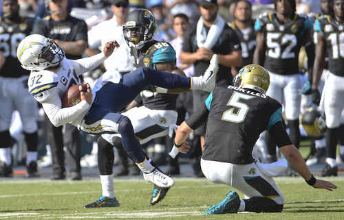 San Diego Chargers free safety Eric Weddle is upended by Jacksonville Jaguars quarterback Blake Bortles after intercepting a Bortles pass during the second half of an NFL football game Sunday, Sept. 28, 2014, in San Diego. Bortles was penalized for tripping Weddle. (AP Photo/Denis Poroy)
