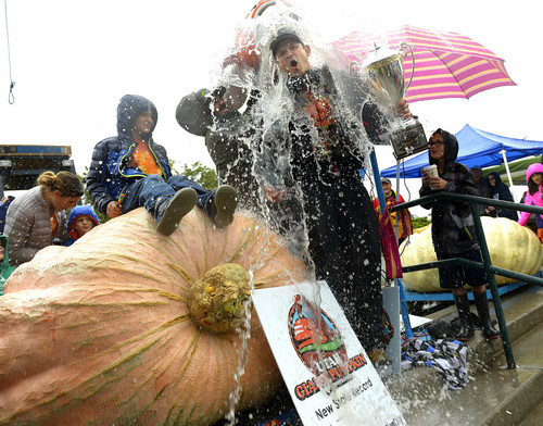 Leah Hogsten  |  The Salt Lake Tribune Matt McConkie is doused in celebration after setting the new state record with his giant pumpkin at 1,731 pounds. The 10th Annual Giant Pumpkin Weigh Off at Thanksgiving Point on Saturday.