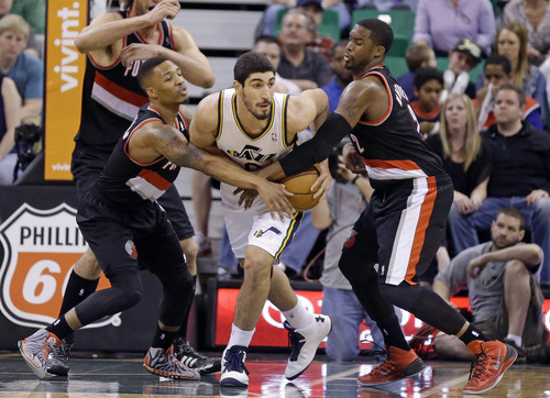 Portland Trail Blazers' Damian Lillard, left, and Wesley Matthews (2) defends against Utah Jazz's Enes Kanter, center, in the fourth quarter of an NBA basketball game on Friday, April 11, 2014, in Salt Lake City. (AP Photo/Rick Bowmer)