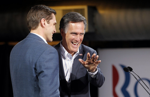 Republican presidential candidate former Massachusetts Gov. Mitt Romney waves on stage with his son Josh, left, at his Colorado caucus night rally in Denver, Tuesday, Feb. 7, 2012. (AP Photo/Gerald Herbert)