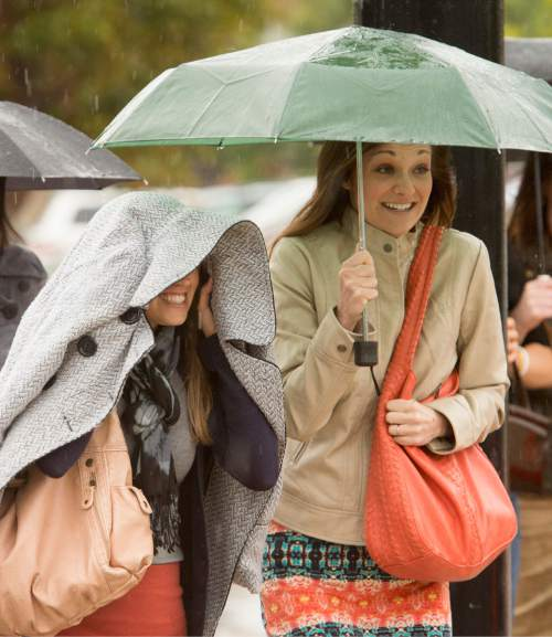 Rick Egan     The Salt Lake Tribune  Kerri Johnson, and Cammie Dickerson, try to keep dry as they make their way to the to the LDS Conference Center, for Women's Conference, Saturday, September 27, 2014.