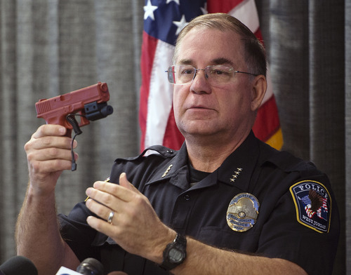 """Steve Griffin     The Salt Lake Tribune   West Jordan Police Chief Doug Diamond demonstrats how a laser aiming device works after narrating the body camera video of an officer-involved shooting of Timothy Peterson on July 10, 2014 during a press conference at the West Jordan Justice Center in West Jordan, Utah Friday, October 3, 2014. Peterson was shot and wounded by police after pointing a metal bar, bent in the shape of a handgun, that had a laser pointer taped to the """"barrel."""""""