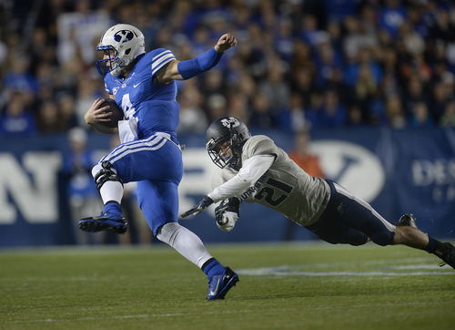 Scott Sommerdorf     The Salt Lake Tribune BYU QB Taysom Hill runs and eludes Utah State Aggies safety Brian Suite (21) during first half play. He later would run a similar play and be injured on a tackle by Suite. Utah State led BYU 28-14 at the half in Provo, Friday, October 1, 2014.
