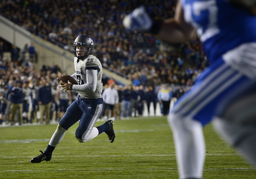 Scott Sommerdorf     The Salt Lake Tribune Utah State Aggies quarterback Darell Garretson runs for a TD during first half play to tie the score at 14-14. Utah State led BYU 28-14 at the half in Provo, Friday, October 1, 2014.