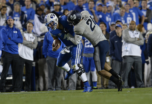 Scott Sommerdorf     The Salt Lake Tribune BYU QB Taysom Hill was injured and left the game after this tackle by Utah State Aggies safety Brian Suite (21) late in the second quarter. Utah State led BYU 28-14 at the half in Provo, Friday, October 1, 2014.