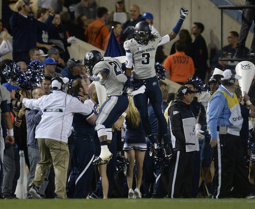 Scott Sommerdorf     The Salt Lake Tribune Utah State Aggies wide receiver Devonte Robinson (3) and USU RB LaJuan Hunt (21) celebrate after a USU TD in the first half. Utah State led BYU 28-14 at the half in Provo, Friday, October 1, 2014.