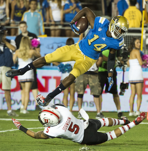 Rick Egan  |  The Salt Lake Tribune  Utes defensive back Chandler Johnson (5) hits UCLA Bruins wide receiver Mossi Johnson (14) for the tackle, at the Rose Bowl in Pasadena, Saturday, October 4, 2014