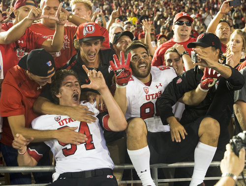 Rick Egan  |  The Salt Lake Tribune  Utah long snapper Chase Dominguez (94) and tight end Westlee Tonga (80) celebrate with Utah fans as the Utes held on for a 30-28 upset over UCLA in Pac-12 action at the Rose Bowl, Saturday, October 4, 2014