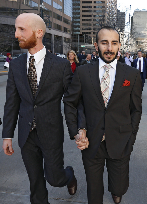 Two of the plaintiffs challenging Utah's gay marriage ban Moudi Sbeity, right, and his partner Derek Kitchen, hold hands as they leave the courthouse following a hearing at the U.S. Circuit Court of Appeals in Denver, Thursday, April 10, 2014.  (AP Photo/Brennan Linsley)