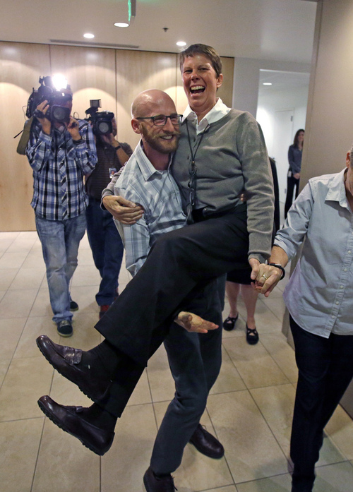 Derek Kitchen carries Kody Partridge as they celebrate following a news conference Monday, Oct. 6, 2014, in Salt Lake City. The U.S. Supreme Court on Monday rejected an appeal from Utah and four other states that had sought to bar weddings between gay couples. (AP Photo/Rick Bowmer)
