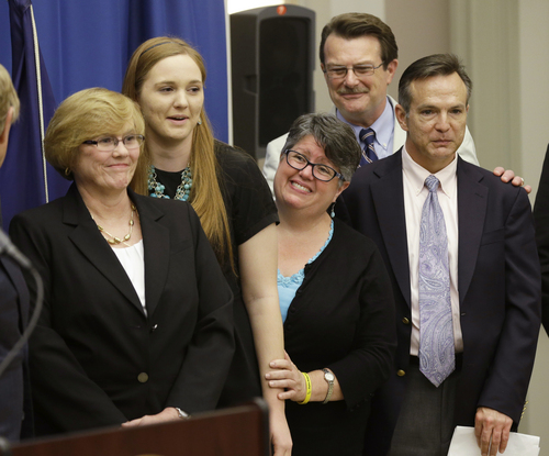 FILE - In this Tuesday May 13, 2014 file photo, plantiff's in the federal suit over Virginia's ban on gay marriage, Mary Townley, left, Emily Schall-Townley, second from left,  Carol Schall, center, Tony London, second from right, and Tim Bostic, right, react to comments during a news conference after a hearing on Virginia's same sex-marriage ban in Richmond, Va.  The Supreme Court cleared the way Monday, Oct. 6, 2014, for an immediate expansion of same-sex marriage by unexpectedly and tersely turning away appeals from five states seeking to prohibit gay and lesbian unions. The court's order effectively makes gay marriage legal now in 30 states.  (AP Photo/Steve Helber)