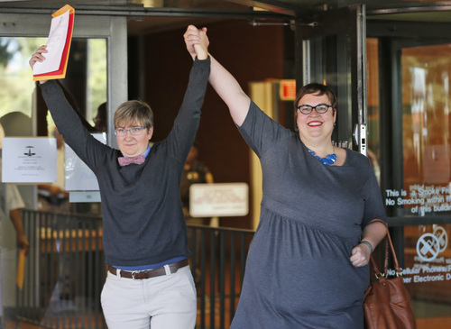 Nicole Pries, left, and Lindsey Oliver hold up their marriage license as they celebrate being one of the first same-sex couples in Virginia to be married outside a Richmond court building in Richmond, Va., Monday, Oct. 6, 2014. The Supreme Court's order turning way appeals from five states seeking to prohibit same-sex marriage has triggered a series of moves in affected states to clear the way for gay and lesbian unions. (AP Photo/Steve Helber)