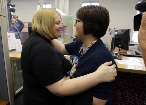 Katie Burris, left, and her partner Evangeline Cook embrace after receiving their marriage license at the Marion County Clerks office in Indianapolis, Monday, Oct. 6, 2014. The U.S. Supreme Court on Monday turned away appeals from Indiana and four other states seeking to prohibit same-sex marriages, paving the way for an immediate expansion of gay and lesbian unions. (AP Photo/Michael Conroy)